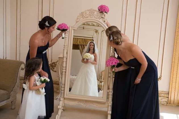 Bridesmaids looking a the bride in a mirrow